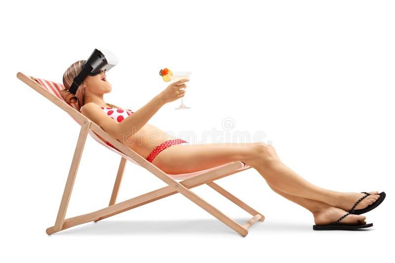 Jonge vrouw in een ligstoel die een VR-hoofdtelefoon met behulp van stock foto