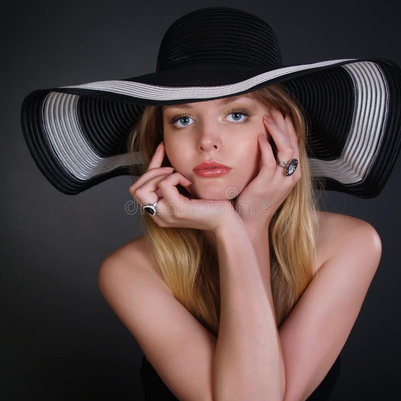 Jonge vrouw in een modieuze zwarte hoed stock fotografie