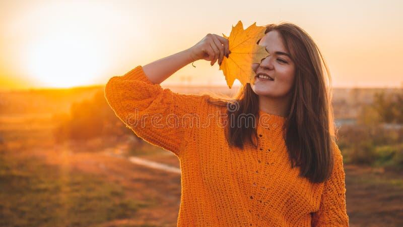 Jonge vrouw in een oranje sweater met met gele bladeren, openluchtportret in zacht zonnig daglicht De herfst Zonsondergang comfor stock foto