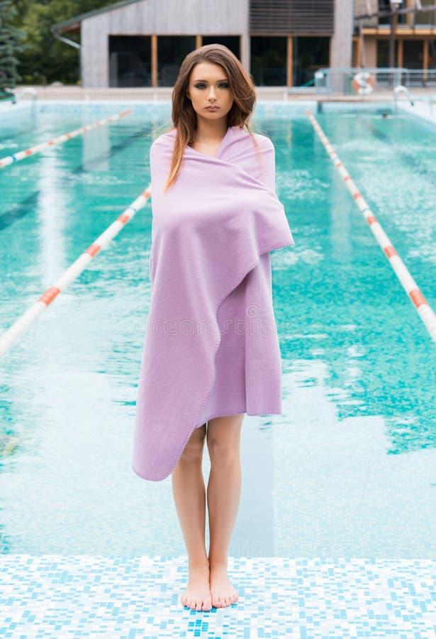 Jonge vrouw in een purpere handdoek naast een zwembad stock afbeeldingen
