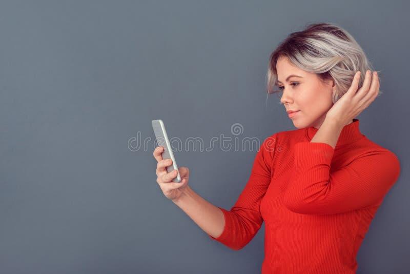 Jonge vrouw in een rode die blouse op grijze smartphone van de muurholding wordt geïsoleerd royalty-vrije stock foto's