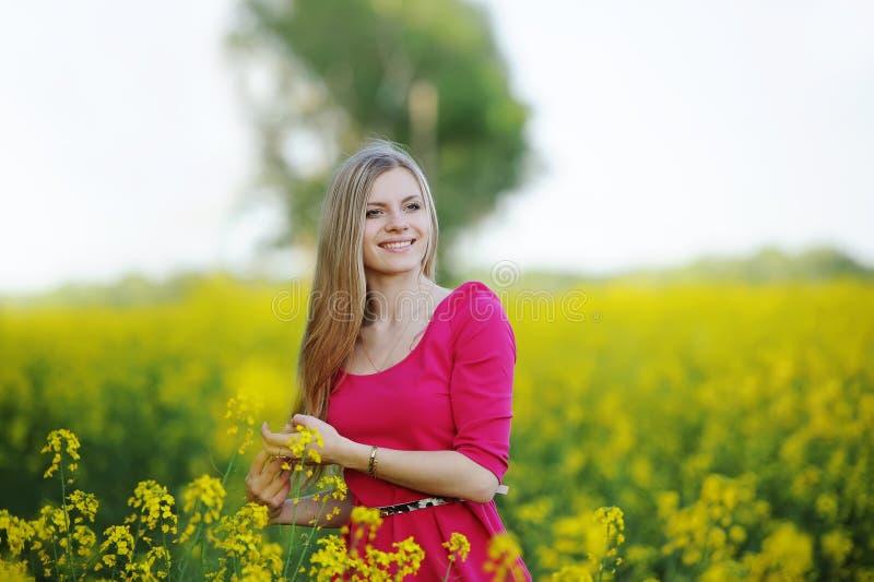 Jonge vrouw in een rode kleding die op het gebied van bloeiende verkrachting toejuichen royalty-vrije stock foto