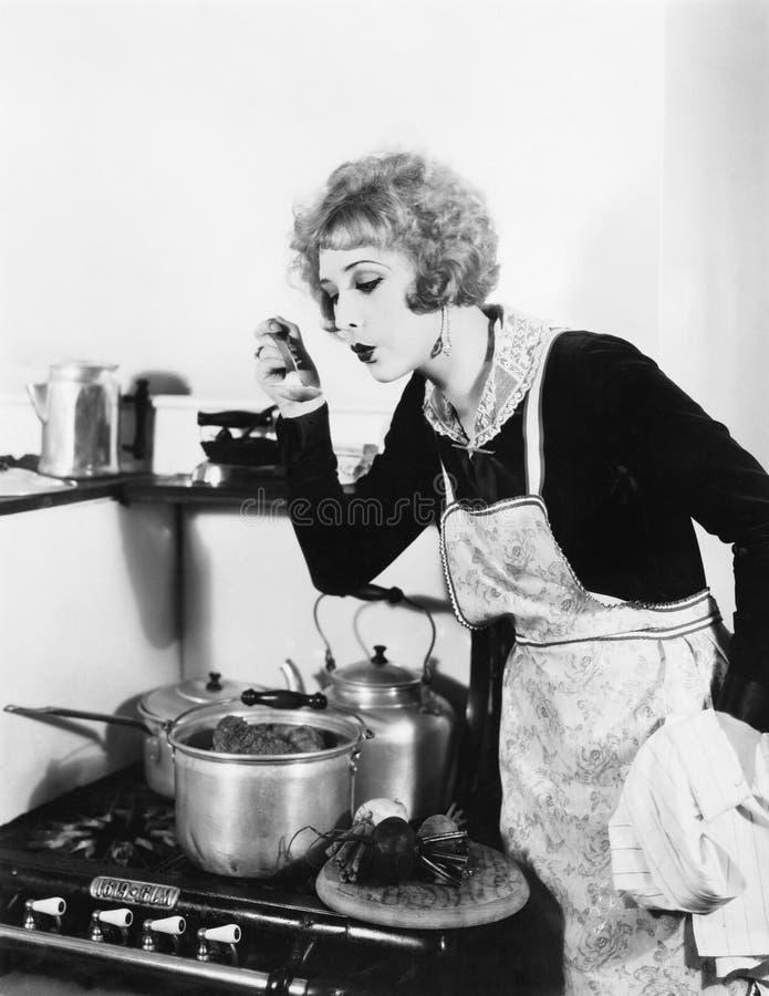 Jonge vrouw in een schort in haar keuken die haar voedsel van een pot proeven (Alle afgeschilderde personen leven niet langer en  royalty-vrije stock foto
