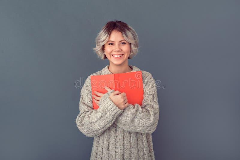 Jonge vrouw in een wollen die sweater op grijs het concepten nieuw boek van de muurwinter wordt geïsoleerd stock afbeelding