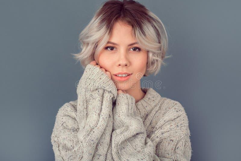Jonge vrouw in een wollen die sweater op grijze het conceptenmanier van de muurwinter wordt geïsoleerd royalty-vrije stock afbeelding