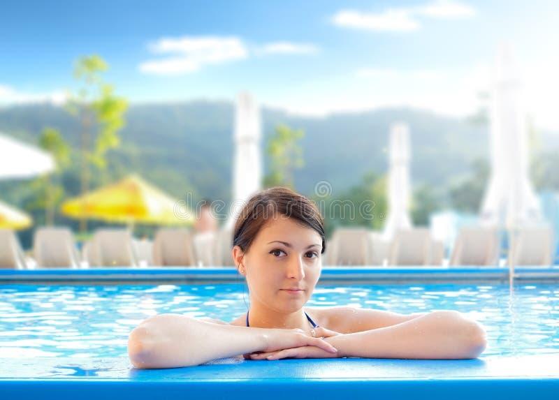 Jonge vrouw in een zwembad stock foto's