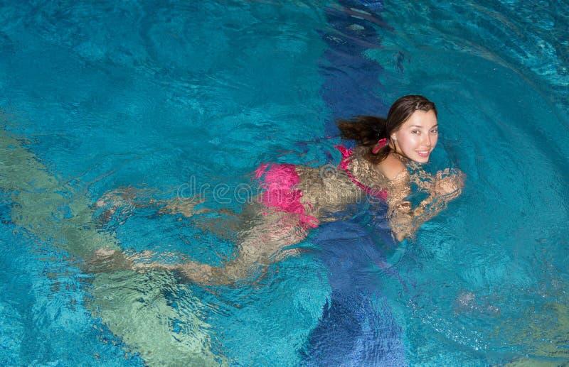 Jonge vrouw in een zwembad stock afbeelding