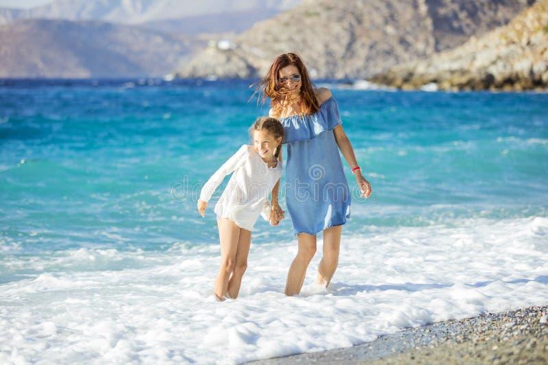 Jonge vrouw en haar dochter die de zomer van dag op strand genieten royalty-vrije stock fotografie