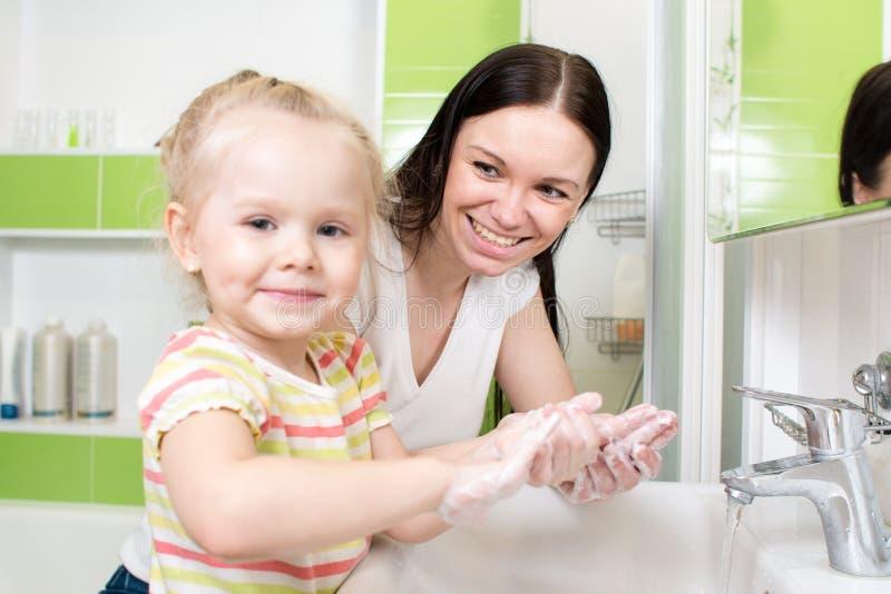 Jonge vrouw en haar handen van de dochterwas met royalty-vrije stock afbeeldingen