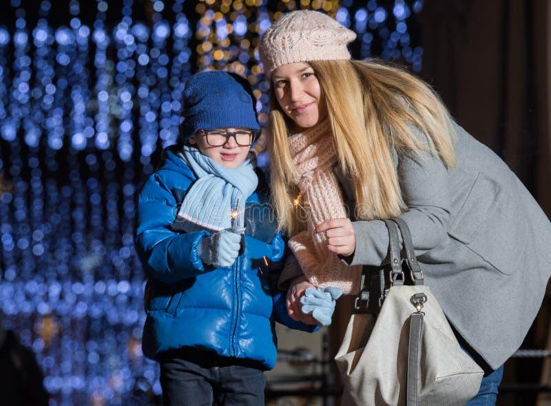 Jonge vrouw en haar kind met Kerstmisfonkelingen stock afbeeldingen