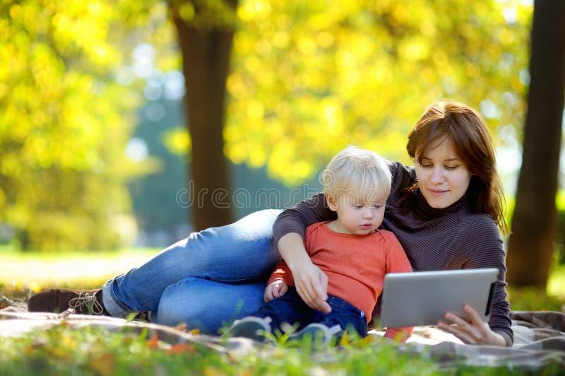 Jonge vrouw en haar weinig zoon die met een digitale tablet speelt royalty-vrije stock afbeeldingen