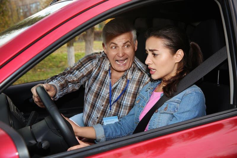 Jonge vrouw en hogere instructeur in auto Ontbreek drijfexamen stock foto