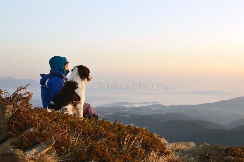 Jonge vrouw en hond het bewonderen zonsopganghoogte in de berg royalty-vrije stock afbeelding