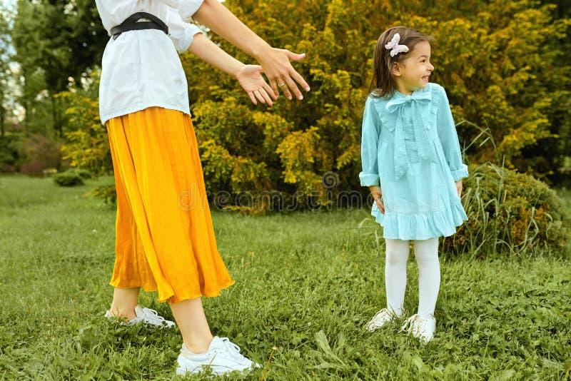 Jonge vrouw en leuk kind die en in het park buiten spelen glimlachen Gelukkig jong geitje die pret met moeder op het groene gras  stock afbeelding