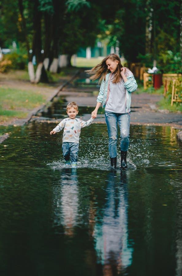 Jonge vrouw en leuke lachende peuterjongen die op een grote vulklei in een de zomerpark lopen na regen stock afbeelding