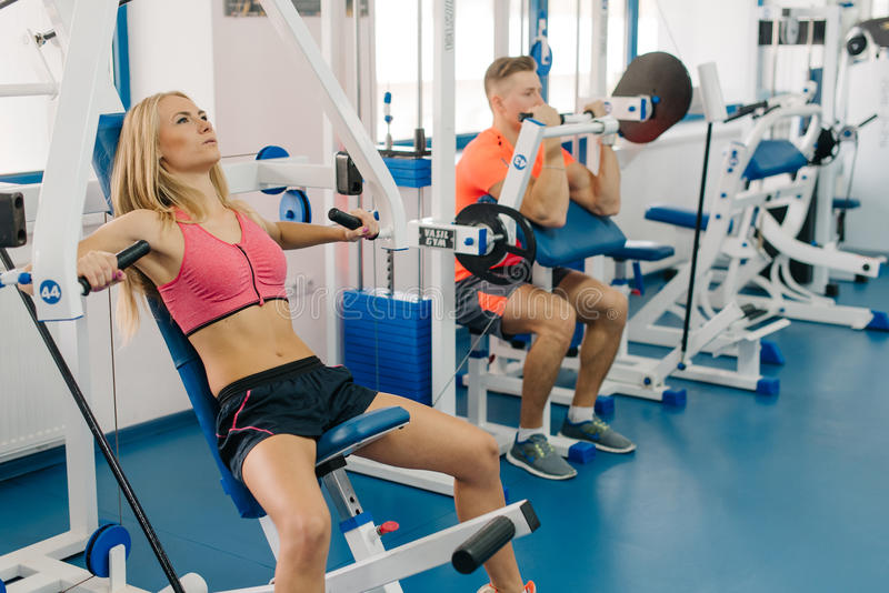 Jonge vrouw en man die in gymnastiek uitwerken Paar die oefeningen voor wapens maken Perfecte organismen royalty-vrije stock afbeeldingen