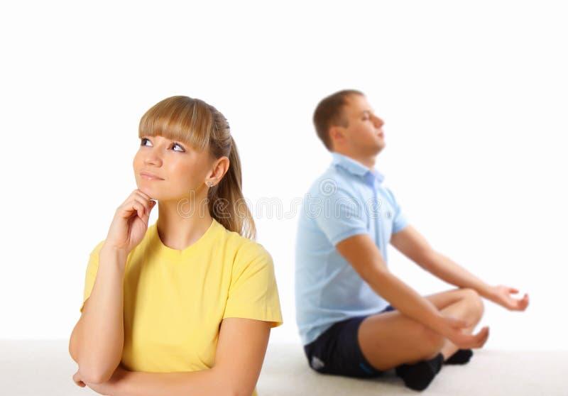 Jonge vrouw en man die yoga op achtergrond doen stock afbeeldingen