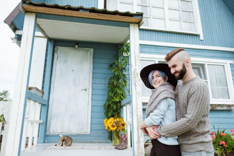 Jonge vrouw en man, familie, die op portiek van dorpshuis zitten met pompoenen stock fotografie