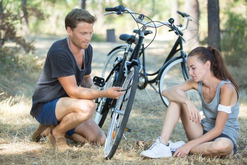 Jonge vrouw en man met fietszitting in park royalty-vrije stock afbeeldingen
