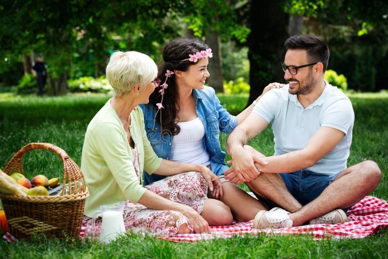 Jonge vrouw en man met grootmoeder het smilling in een park op een zonnige dag stock afbeeldingen