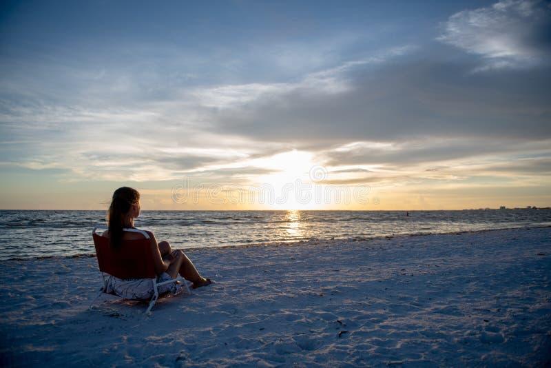 Jonge vrouw en zonsondergang op het strand stock afbeelding