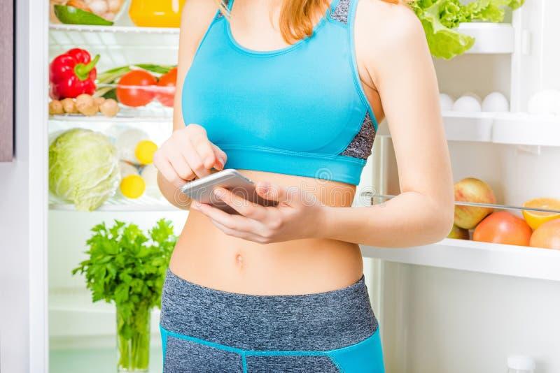 Jonge vrouw gebruikend een smartphone app en blijvend dichtbij het koelkasthoogtepunt van gezond voedsel royalty-vrije stock afbeeldingen
