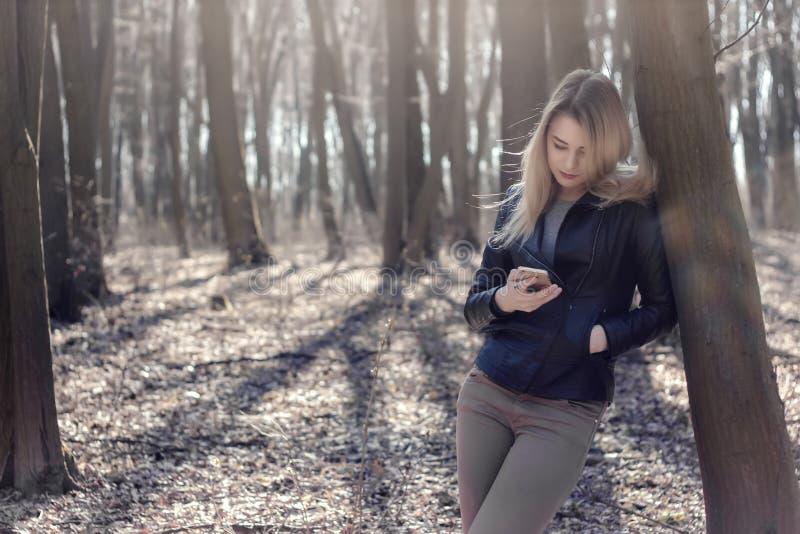 Jonge vrouw gebruikend mobiele telefoon aan het searhing en lezend nieuws stock afbeelding