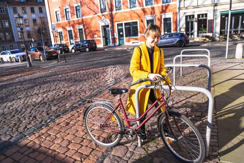 Jonge vrouw in gele laag die zich met fiets bevinden royalty-vrije stock foto's