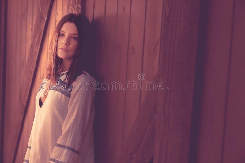 Jonge vrouw gevlekt in licht van staldeur royalty-vrije stock afbeeldingen