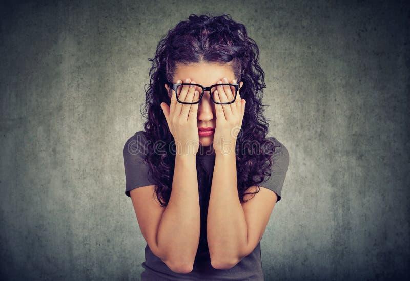 Jonge vrouw in glazen die gezichtsogen behandelen met beide handen stock afbeelding