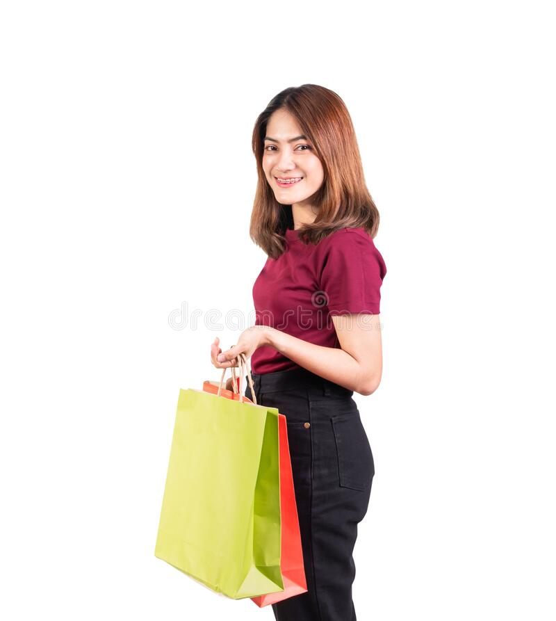 Jonge vrouw glimlachend met papieren tassen groen en oranje winkelen geïsoleerd op witte achtergrond en kijkend camera stock afbeelding
