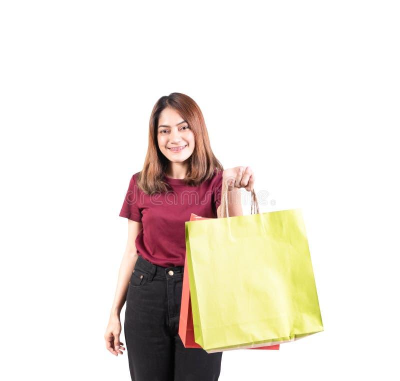 Jonge vrouw glimlachend met papieren tassen groen en oranje winkelen geïsoleerd op witte achtergrond en kijkend camera royalty-vrije stock afbeeldingen