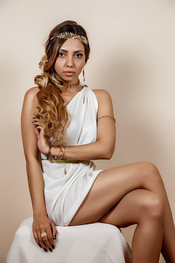Jonge vrouw in Griekse stijlkleding over beige achtergrond stock foto