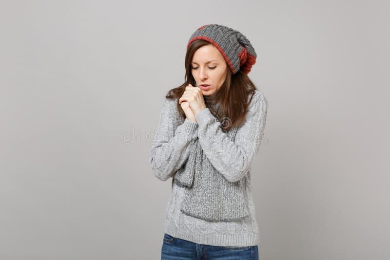Jonge vrouw in grijze sweater, hoed en sjaal met verminderd hoofd die haar handen verwarmen die op grijze achtergrond worden geïs royalty-vrije stock afbeeldingen