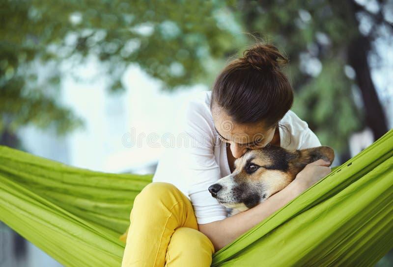 Jonge vrouw in groene hangmat met leuke hond Welse Corgi in een park in openlucht Mooi gelukkig wijfje in wit overhemd royalty-vrije stock afbeelding