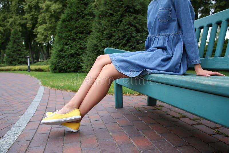 Jonge vrouw in gumshoes die op bank in openlucht rusten royalty-vrije stock fotografie
