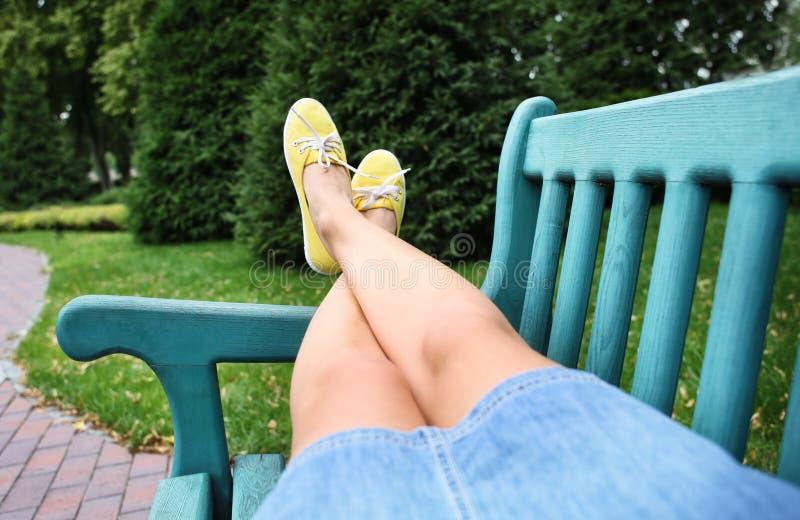 Jonge vrouw in gumshoes die op bank in openlucht rusten stock foto's