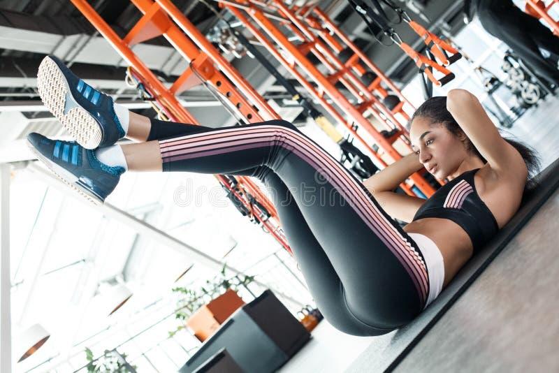 Jonge vrouw in gymnastiek sportieve levensstijl die op mat liggen die benenoefening opheffen stock foto's