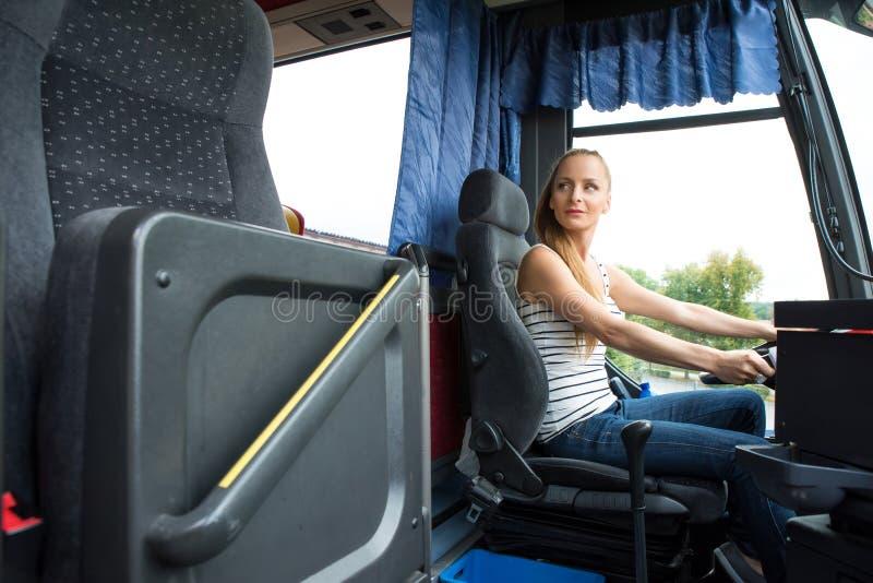 Jonge vrouw in haar functie als buschauffeur stock afbeelding