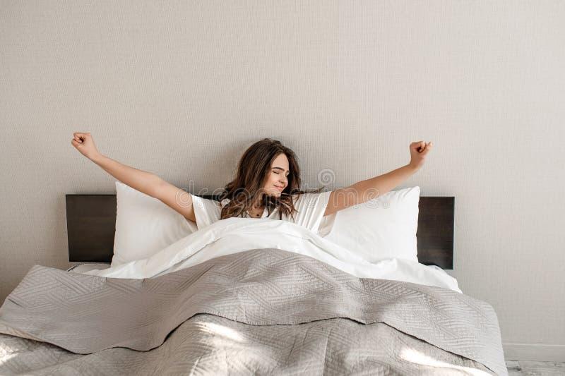 Jonge vrouw in het bed De glimlachende mooie vrouw in pyjama's is ontwaken, goedemorgen in de slaapkamer stock afbeeldingen
