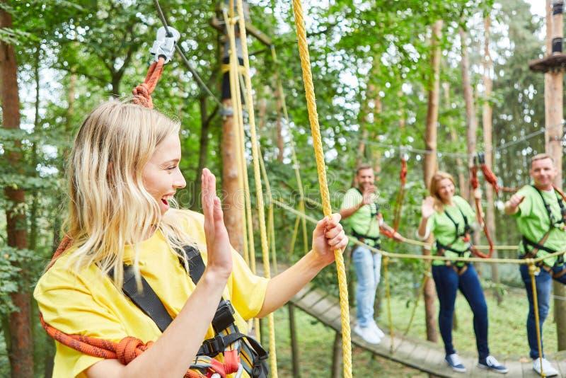 Jonge vrouw in het beklimmen van cursus in hoge draadtuin stock afbeeldingen