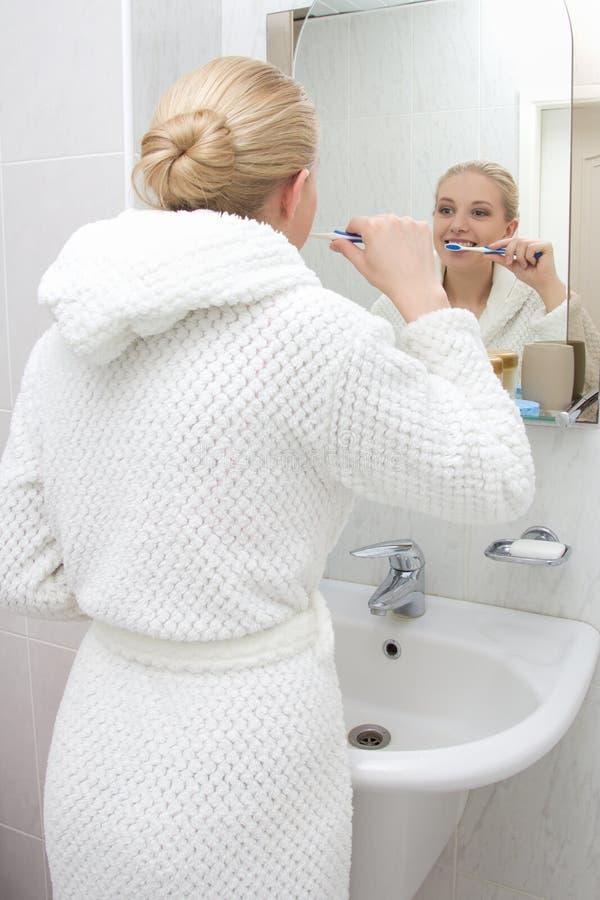 Jonge vrouw het borstelen tanden en het bekijken spiegel in badkamers royalty-vrije stock afbeelding