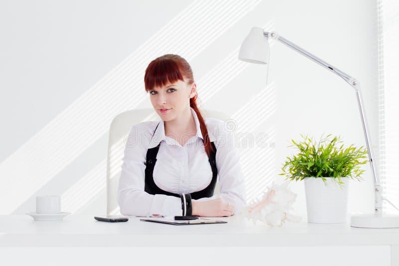 Jonge vrouw in het bureau stock foto