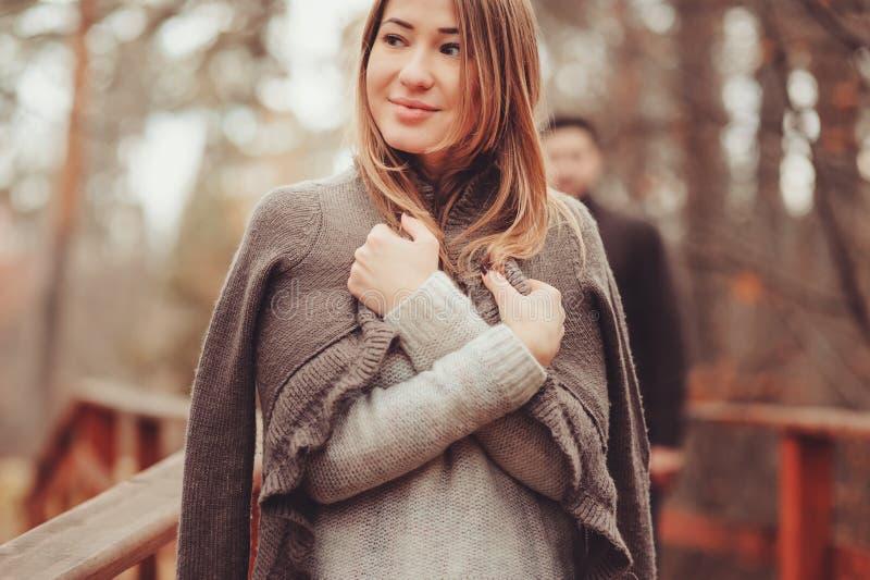 Jonge vrouw in het comfortabele warme cardigan lopen openlucht in de herfstbos, met vriend op achtergrond royalty-vrije stock afbeeldingen
