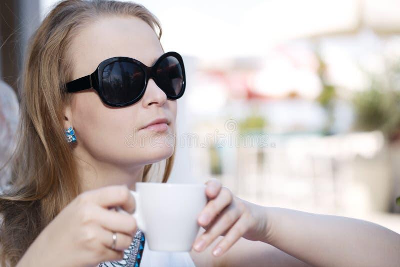 Jonge vrouw het drinken koffie stock foto's