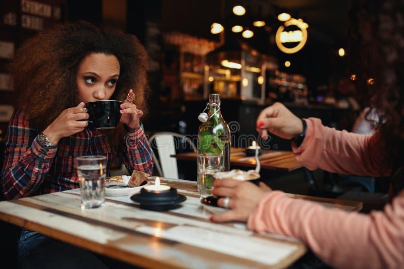 Jonge Vrouw het Drinken Koffie bij Koffie royalty-vrije stock foto's