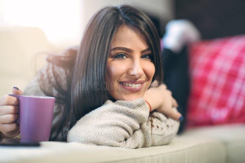 Jonge vrouw het drinken koffie die thuis, op de laag liggen royalty-vrije stock foto