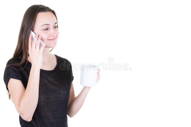 Jonge vrouw het drinken koffie en het gebruiken van haar mobiele telefoon in witte ruimte als achtergrond en exemplaar royalty-vrije stock afbeelding