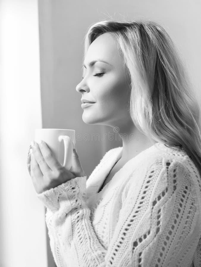 Jonge vrouw het drinken koffie en het kijken het aan het venster royalty-vrije stock afbeelding