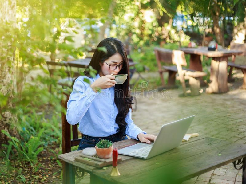 Jonge vrouw het drinken koffie en het werken met laptop in tuin royalty-vrije stock afbeelding